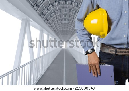 Engineer holding yellow helmet for workers security on background of new highrise apartment buildings and construction cranes on background of evening sunset cloudy sky Silhouette Crane lifts load. - stock photo
