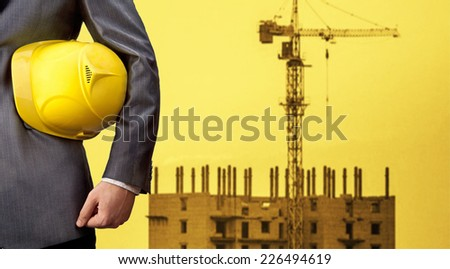 engineer holding yellow helmet for workers security on background of new highrise apartment buildings and construction cranes on background of evening sunset cloudy sky Silhouette Crane lifts load - stock photo