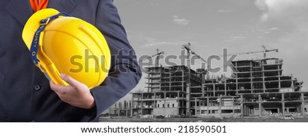 engineer holding yellow helmet for workers security on background of new highrise buildings and construction cranes on background  - stock photo