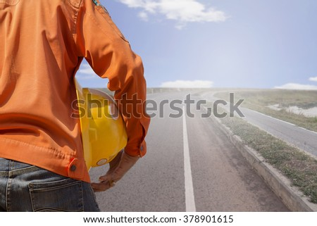 engineer holding yellow helmet  standing on straight road.  - stock photo
