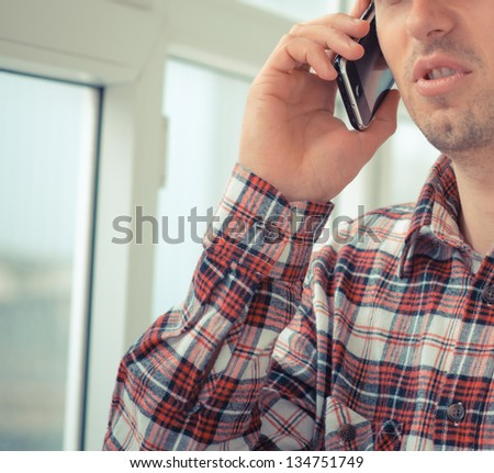 engineer in a helmet uses a smart phone - stock photo