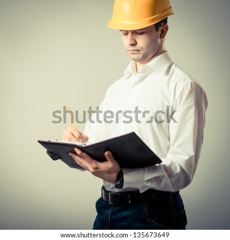 engineer in a helmet writes in a notebook  on a gray background - stock photo