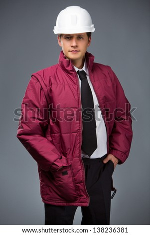 engineer in a red jacket and a white helmet hand in pocket - stock photo