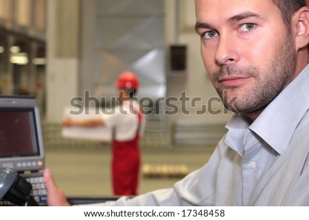 engineer in factory,worker with box in background - stock photo