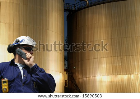 engineer in front of two sunlit fuel-storage tanks, concept industrial shot. - stock photo