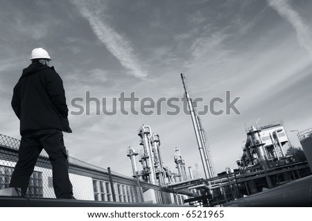 engineer in hard-hat overlooking large refinery plant all in a duplex toning - stock photo