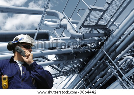 engineer in hard-hat with large refinery pipelines in background, blue toning background - stock photo