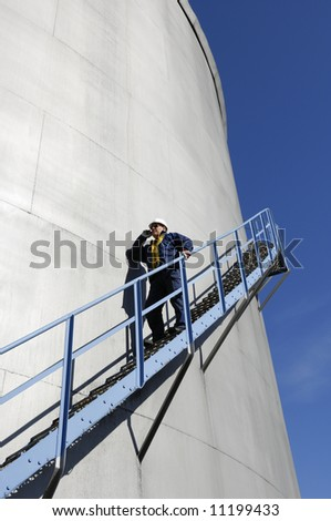engineer in hardhat, walking along fuel-storage tank - stock photo