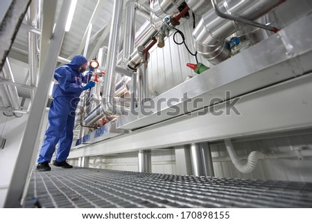 engineer  in mask,gloves,goggles and blue uniform controlling technological system  - stock photo