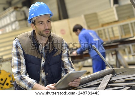 Engineer in metallurgical factory using tablet - stock photo