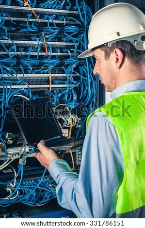 engineer in network server room solving problems - stock photo