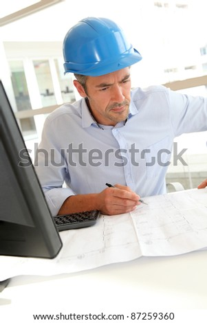 Engineer in office working on construction plan - stock photo