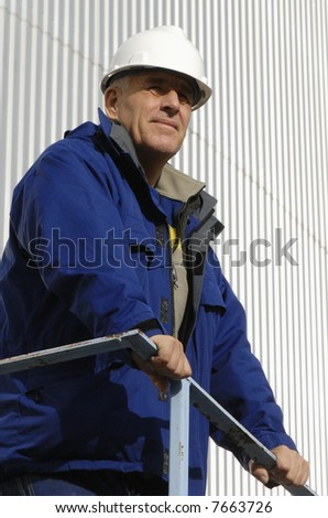engineer in profile, wearing hard-hat, standing against metal background - stock photo