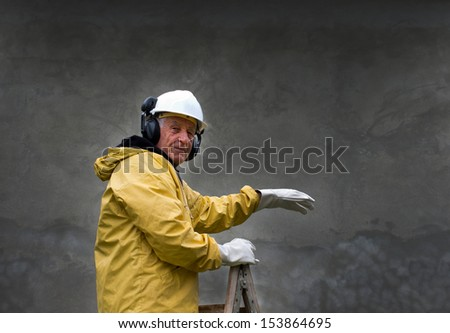 Engineer in safety suit stands on ladder - stock photo