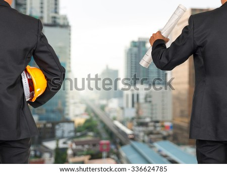 engineer in suit holding orange helmet and blueprint on abstract Blurred photo of sky train with cityscape background, business busy concept - stock photo