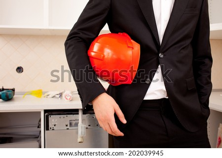 engineer in the new interior, with protective helmet under his arm - stock photo