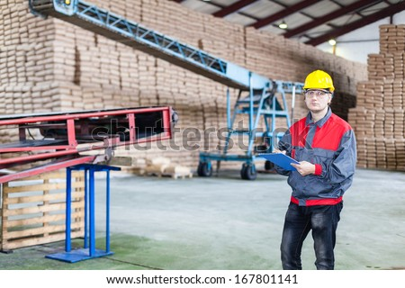 Engineer in the sugar factory. In a background are bags with sugar.
