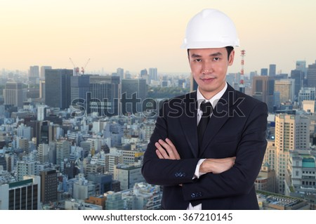 engineer in white helmet with arms crossed, city background