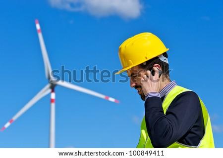 Engineer in Wind Turbine Power Generator talk at phone Station, Italy - stock photo