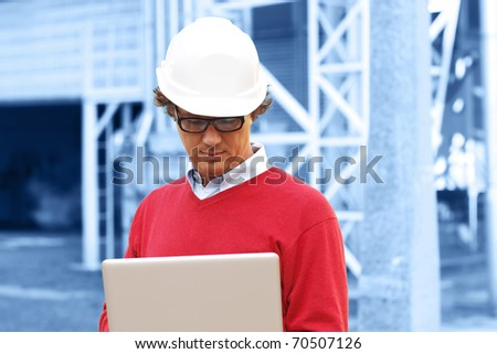 Engineer Inside Power Plant With Laptop (blue toned background)
