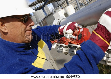engineer inside refinery turning pipeline wheels - stock photo