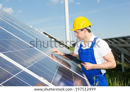 Engineer inspecting solar panels at energy park in front of wind turbine - stock photo