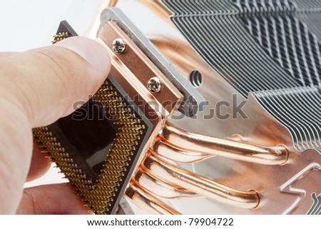 Engineer installing computer processor to big cooler - stock photo