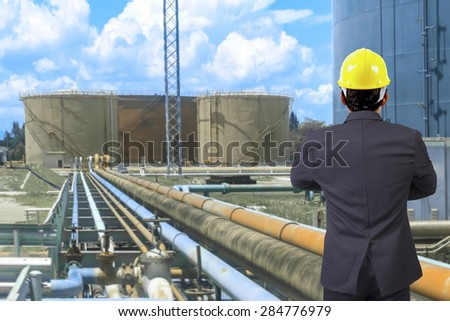 Engineer looking for working at pipe line connection to oil tanks in petrochemical oil refinery