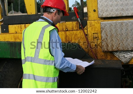 Engineer looking thoughtful, examining the plans, wearing a red safety helmet and a high visibility yellow vest at the work site.