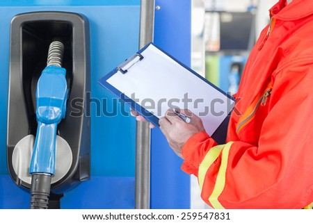 engineer maintaining record with gasoline pump nozzles - stock photo
