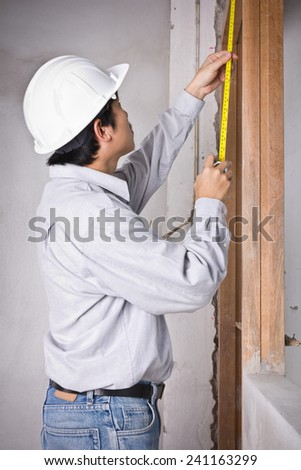 Engineer man wearing white hard hat and checking by tape measure at construction site works - stock photo