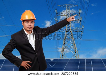 Engineer man with solar panel against high voltage towers background. - stock photo