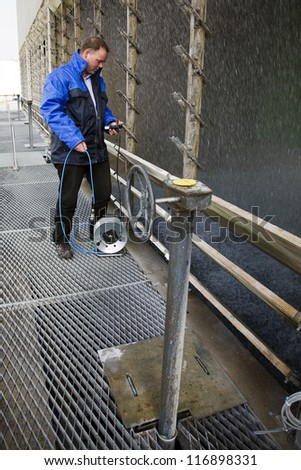 Engineer measuring the basin and hydrostatic level of a cooling tower. - stock photo