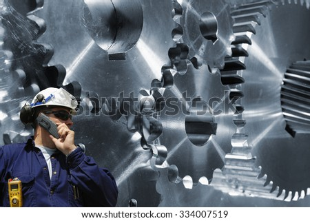 engineer, mechanic with large cogwheels and gears machinery - stock photo