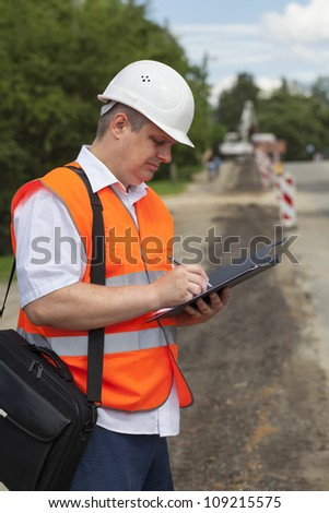 Engineer near the road repair work - stock photo