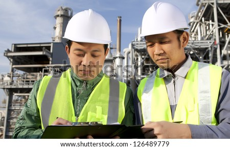 engineer oil gas industry discussion with large refinery on the background - stock photo