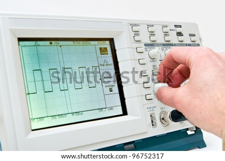 Engineer Operating a Digital Oscilloscope