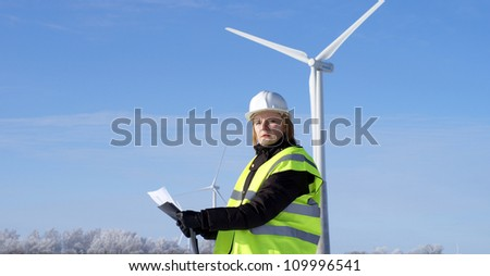 engineer or architect with white safety hat and wind turbines on background - stock photo