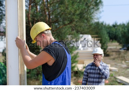 Engineer or foreman watching a builder at work as he installs an insulated wall panel on a new build house - stock photo