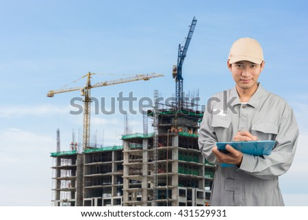 Engineer or technician write book with buildings and construction cranes on background - stock photo