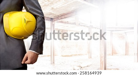 engineer or worker hand holding yellow helmet for workers security over empty old building inside concrete house background Copy Space for inscription Idea oe concept of safety Sunny day light  - stock photo