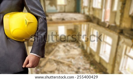 engineer or worker hold in hand yellow plastic helmet for workers security inside against the interior of an old ruined brick building with windows Day light Empty space for inscription  - stock photo