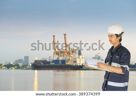 Engineer over Container Cargo freight ship with working crane bridge in shipyard at early morning.