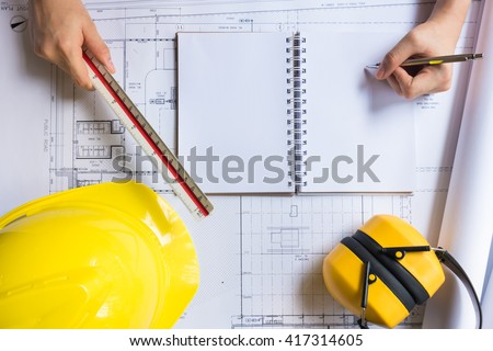 Engineer person working to building design concept with yellow hard hat. Top view from above with copy space. - stock photo
