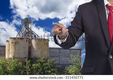 engineer pushing on a touch screen interface working at high building construction site against blue sky with in concept ecology and real estate - stock photo