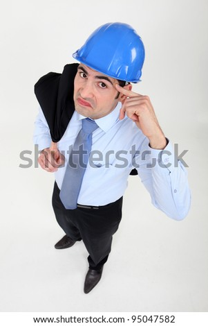 Engineer putting his finger to his head - stock photo