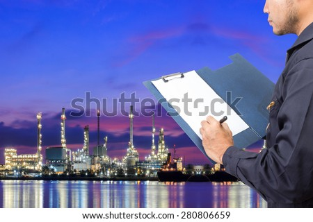 Engineer recording maintenance working at oil refinery petrochemical industrial plant at twilight - stock photo