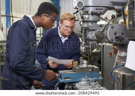 Engineer Showing Apprentice How to Use Drill In Factory - stock photo