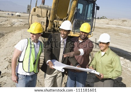 Engineer showing blueprint at construction site - stock photo