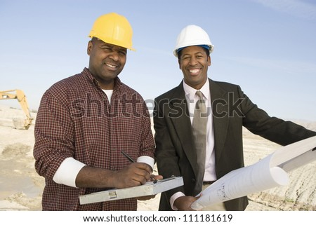 Engineer showing blueprint for a worker at construction site - stock photo
